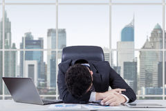 Frustrated worker sleeping in the office. Male entrepreneur looks frustrated and sleeping in the workplace with laptop and documents on desk near the window Royalty Free Stock Photography