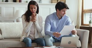 Frustrated young couple stressed about high mortgage rates doing paperwork