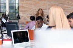 Frustrated young african entrepreneur with sad grimace in front of his laptop in office. Noticed a big mistake he did, holding his face with arms palms Royalty Free Stock Photography