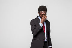 Frustrated young African man massaging nose and keeping eyes closed while standing against grey background Stock Photography