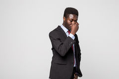 Frustrated young African man massaging nose and keeping eyes closed while standing against grey background. Stressed and tired. Frustrated young African man royalty free stock photography