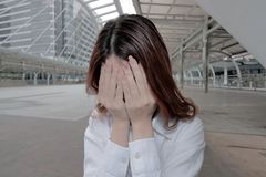 Frustrated young Asian businesswoman with hands on face feeling tired with job. Worried business concept. Stock Photo