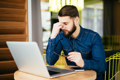 Frustrated young beard man massaging his nose and keeping eyes closed while sitting at his working place in office. Feeling exhausted. Frustrated young beard man stock image
