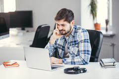 Frustrated young bearded man thinking and sitting Royalty Free Stock Photos