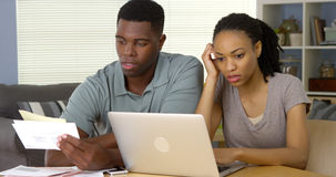 Frustrated young Black couple going over bills and finances online Royalty Free Stock Photography