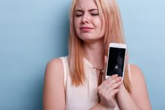 A frustrated girl, emotionally holds a broken mobile phone in her hand. Close-up. Blue background. A frustrated young blonde girl, of European appearance royalty free stock image