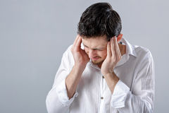 Frustrated young brunette man in shirt with headache on gray bac Royalty Free Stock Photography