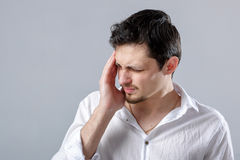 Frustrated young brunette man in shirt with headache on gray bac Stock Image