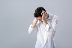 Frustrated young brunette man in shirt with headache on gray bac Royalty Free Stock Photo