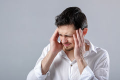 Frustrated young brunette man in shirt with headache on gray bac Royalty Free Stock Image