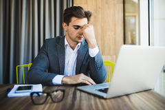 Frustrated young business man working on laptop computer at office. Frustrated business man working on laptop computer at office Royalty Free Stock Image