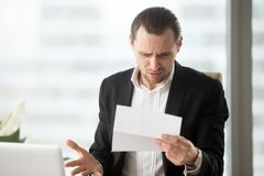 Frustrated young businessman looking at confusing letter in offi Stock Image