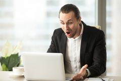 Frustrated young businessman looks at laptop screen screaming in. Anger at workplace in office. Unexpected high bill, unpaid debt, failing financial report, tax Royalty Free Stock Images