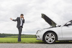 Frustrated young businessman using cell phone by broken-down car at countryside stock image