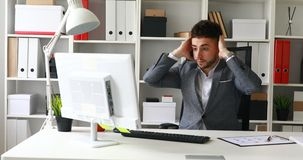 Frustrated young businessman working on computer.