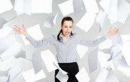 Desperate businesswoman with falling paper documents Royalty Free Stock Images