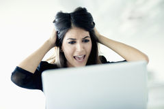 Frustrated young businesswoman holding her head and staring at the laptop Stock Image
