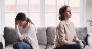 Frustrated young daughter and mature mother feel upset having conflict