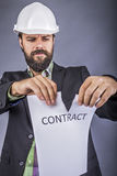 Frustrated young engineer with hardhat  tearing apart a contract Royalty Free Stock Images
