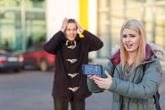 A frustrated girl holds a broken mobile phone, in the background a guy holds his head. A frustrated young European blonde girl holds a broken mobile phone in stock images