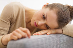 Frustrated young housewife sitting on couch Royalty Free Stock Image