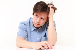 Frustrated young man pulling his hair Stock Photo