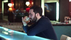Frustrated young man sitting at the bar counter and holding glass stock video