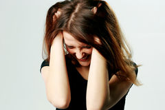 Frustrated young screaming woman pulling her hair. Portrait of a frustrated young screaming woman pulling her hair on gray background Royalty Free Stock Photography