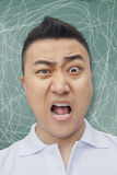 Frustrated young student in front of blackboard, making a face Royalty Free Stock Photo