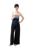 Frustrated young trendy woman in wide-leg pants typing message on cellphone Royalty Free Stock Photos