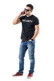 Frustrated young undercover police officer talking on the mobile phone. Full body length portrait isolated on white studio background Stock Images