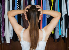 Frustrated young woman cannot decide what to wear from her close stock photos