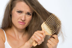 Frustrated young woman combing hair. Isolated on white background Royalty Free Stock Photo