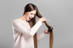 Woman with hairbrush. Frustrated young woman combing tangled long natural hair with hairbrush royalty free stock photography