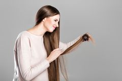 Woman with hairbrush. Frustrated young woman combing tangled long natural hair with hairbrush royalty free stock images