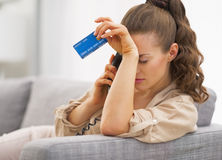 Frustrated young woman with credit card and talking phone. In living room Stock Photos