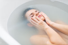 Frustrated young woman laying in bathtub Stock Images