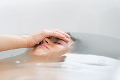 Frustrated young woman laying in bathtub Royalty Free Stock Photos