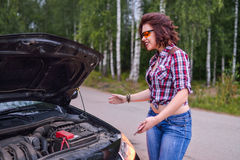 Frustrated young woman looking at broken down car engine.  Stock Images