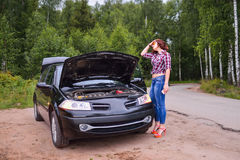 Frustrated young woman looking at broken down car engine Stock Photos