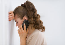 Frustrated young woman talking mobile phone Royalty Free Stock Image
