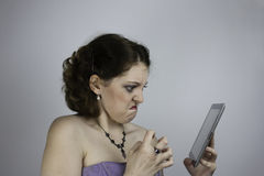 Frustrated young woman uses tablet Stock Images