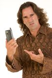 Frustration. Mid-aged man with long hair apparently frustrated with his cell-phone Royalty Free Stock Image