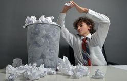 Frustration. Young businessman next to stack of crumpled paper Royalty Free Stock Image