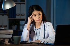 Frustration female doctor looking at computer. Frustration young female doctor sitting in her consulting room and looking at computer at late night. mixed race Stock Image
