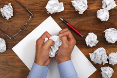 Frustration stress and writers block. Crumpled paper and businessman tearing up another paper ball for the pile Stock Photo