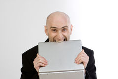 Frustration At Work. A businessman showing his frustration by biting his laptop computer Royalty Free Stock Photos