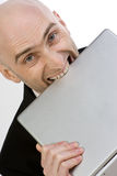 Frustration At Work. A businessman showing his frustration by biting his laptop computer Stock Photo