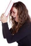 Frustrato con il libro contro la testa Immagini Stock