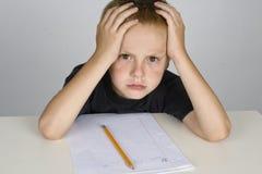 Frustreerde weinig jongen die thuiswerk doet Stock Afbeeldingen